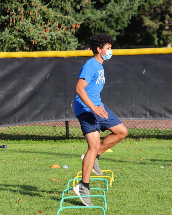 Freshman Beruk Sims jumps over mini hurdles at practice. The track team held a masked practice on October 14.