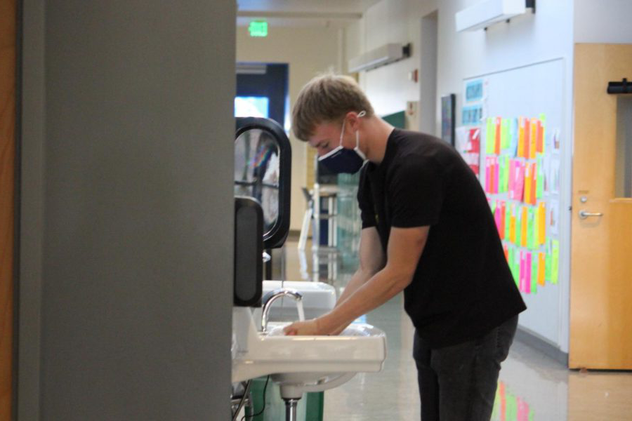 Henry Buscher washes his h和s in the new sinks in the Classroom Building.